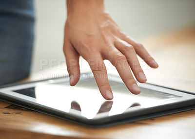 Buy stock photo Cropped shot of a businessman's hand touching the screen on a digital tablet
