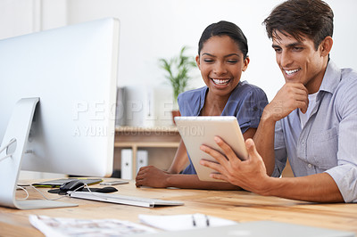 Buy stock photo Cropped shot of two young colleagues using a digital tablet