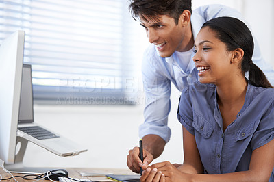Buy stock photo Cropped shot of two young colleagues working at a desk