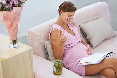 Buy stock photo A happy pregnant woman satisfying a craving for pickles while reading on the sofa