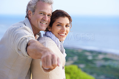Buy stock photo A loving mature couple standing with their arms extended against a pretty vista