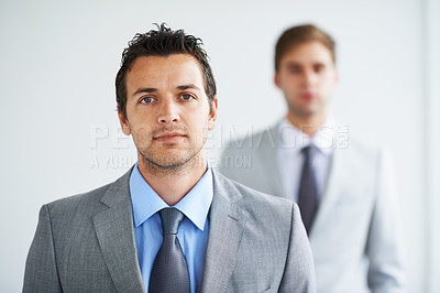 Buy stock photo Portrait of a handsome young executive with a colleague blurred in the background