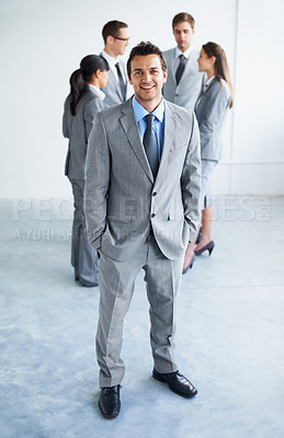 Buy stock photo Full body image of a confident young businessman with his team standing in the background