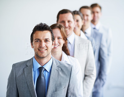 Buy stock photo Portrait of a group of smiling businesspeople standing in a line