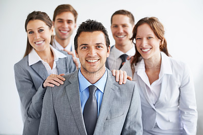 Buy stock photo A group of businesspeople standing proudly with their leader as he smiles at the camera