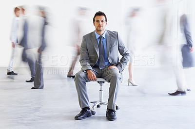 Buy stock photo Conceptual portrait of a young executive sitting as colleagues stream passed him hastily