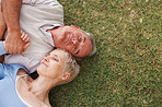 Top view of a senior holding hands while lying on grass