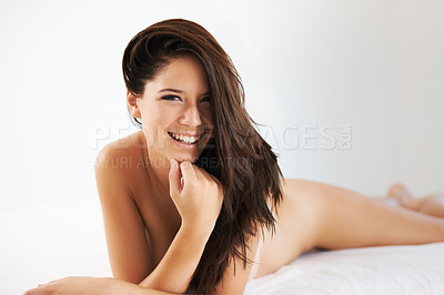 Buy stock photo Cropped shot of a sexy young woman posing nude on a bed