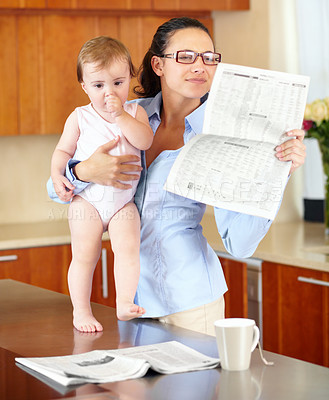 Buy stock photo Shot of a stressed-looking single mom holding her baby while trying to read the paper