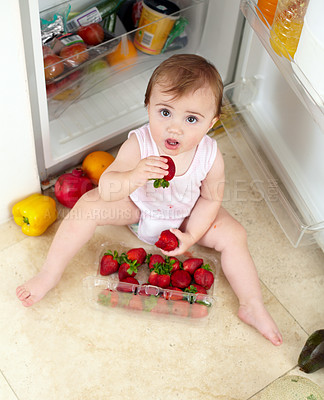 Buy stock photo High angle shot of an adorable toddler eating a strawberry after raiding the fridge