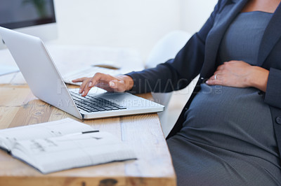 Buy stock photo Cropped image of a pregnant businesswoman working on her laptop in the office