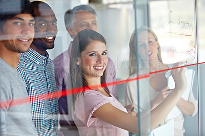 Buy stock photo Portrait of a group of businesspeople writing down their plans on a glass pane