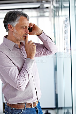Buy stock photo A mature businessman looking thoughtful while talking on his phone