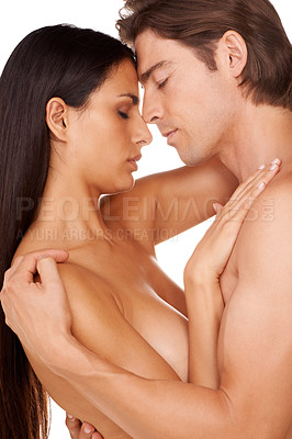 Buy stock photo Studio shot of a naked couple enjoying a sensual moment against a white background