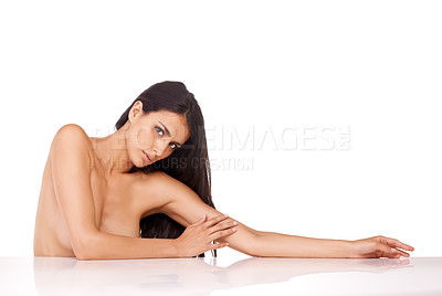 Buy stock photo Studio shot of a beautiful topless woman leaning on a counter against a white background