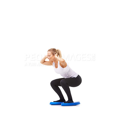 Buy stock photo Full length studio shot of a young woman doing squatting exercises isolated on white