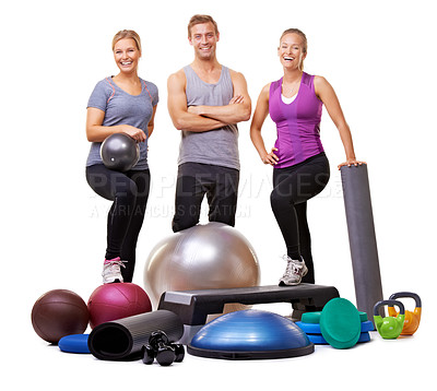 Buy stock photo Studio portrait of a group of sporty people standing behind a pile of small gym equipment