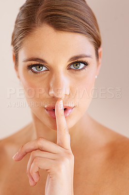 Buy stock photo Studio portrait of an attractive young woman making a shh gesture at the camera