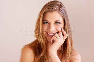 Buy stock photo Studio portrait of an attractive young woman with her hand on her chin smiling at the camera