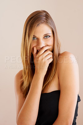 Buy stock photo Studio portrait of an attractive young woman  with her hand over her mouth as she laughs playfully
