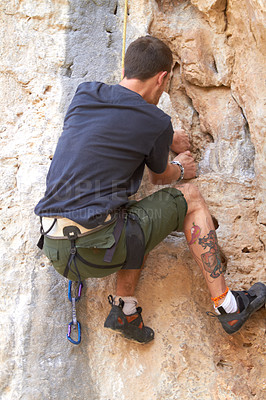 Buy stock photo Rearview of a tattooed rock climber clinging onto a crack in the rockface
