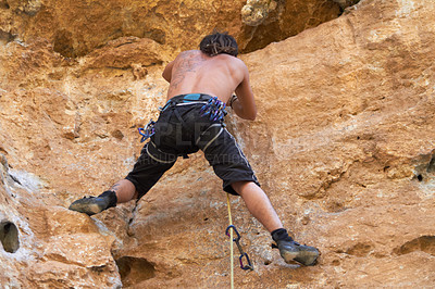 Buy stock photo Rearview of rugged bare chested rock climber climbing a rockface
