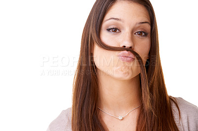 Buy stock photo Studio shot of a beautiful young woman playfully creating a mustache from her own hair against a white background