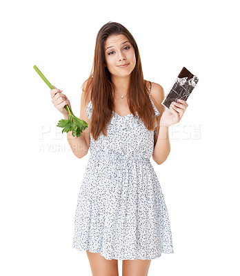 Buy stock photo An attractive young woman deciding between a stick of celery and a slab of chocolate