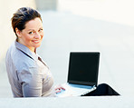 Happy mature business woman using a laptop outdoors