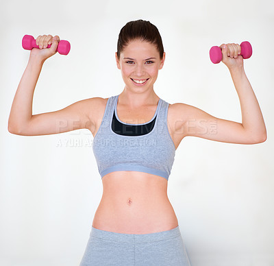 Buy stock photo Portrait of an attractive young woman in sporty clothing training with dumbbells