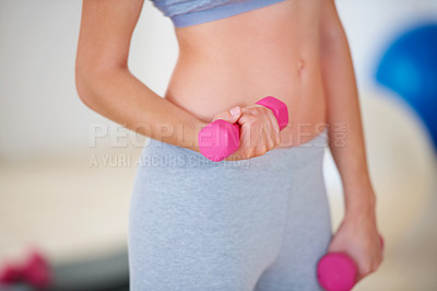 Buy stock photo Cropped image of a woman training with weights in the gym