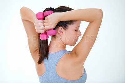 Buy stock photo Rearview of an attractive young woman doing bicep curls with a dumbbell