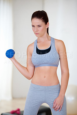 Buy stock photo A beautiful young woman training with dumbbells and looking confident