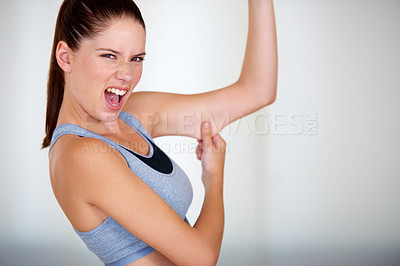 Buy stock photo Portrait of an attractive young woman grabbing her arm fat and looking upset