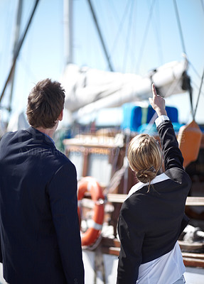 Buy stock photo Young business people looking at a yacht together at the marina