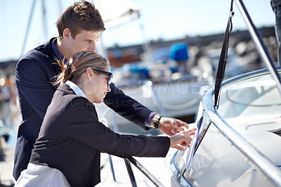 Buy stock photo Young business couple looking at a yacht together at the marina
