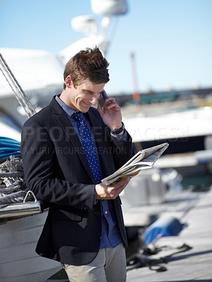 Buy stock photo Young businessman reading the newspaper while on his cellphone at the marina