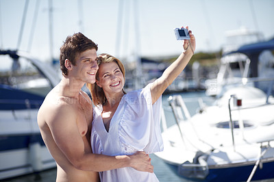 Buy stock photo Young couple taking a snapshot of themselves at the marina
