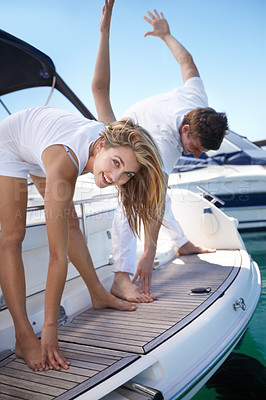 Buy stock photo Young couple exercising together on a yacht