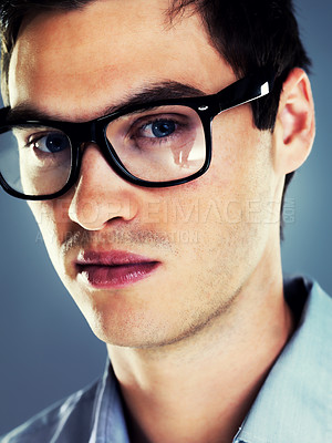 Buy stock photo Closeup portrait of a handsome young man wearing glasses against grey background
