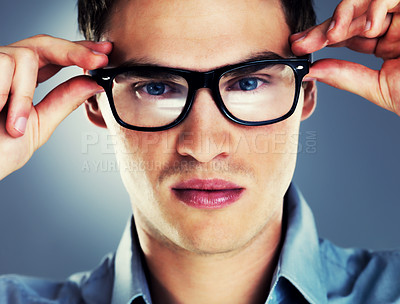 Buy stock photo Closeup portrait of a smart young guy wearing glasses against grey background