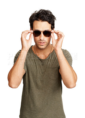 Buy stock photo A trendy young man putting on sunglasses