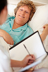Happy elderly woman in bed getting a checkup a doctor