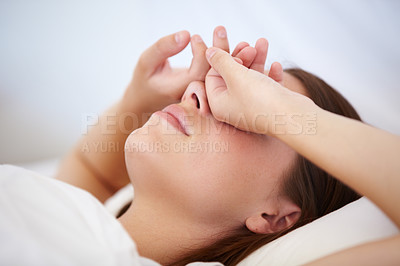 Buy stock photo A young woman lying in bed with her hands over her eyes