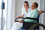 Elderly woman on a wheel chair with a nurse by her