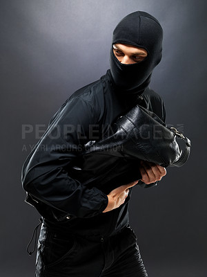 Buy stock photo Portrait of a young male burglar running with a handbag against grey background