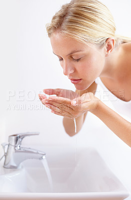 Buy stock photo Shot of an attractive young woman washing her face with water over a sink