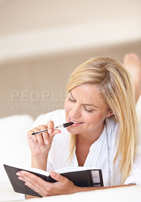 Buy stock photo A gorgeous young woman writing in her journal