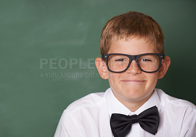 Buy stock photo A happy young schoolboy with a bow-tie smiling at the camera in front of a blackboard - copyspace