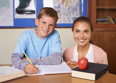 Buy stock photo A supportive young teacher sitting next to her student while he writes in a book